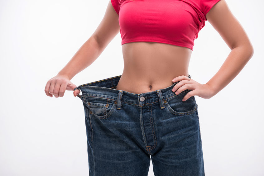34868822 - close-up of slim waist of young woman in big jeans showing successful weight loss, isolated on white background, diet concept